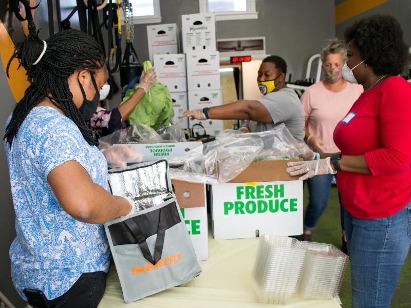 People packing produce into food bags at Bourne2Fly Fitness in Washington, DC